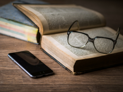 glasses on opened book, mobile phone